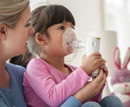 Mutter mit Kind auf dem Schoß. Beide halten das Inhalationsgerät mit Mund-Nasenmaske so dass das Kind inhalieren kann. - air-be-c Medizintechnik