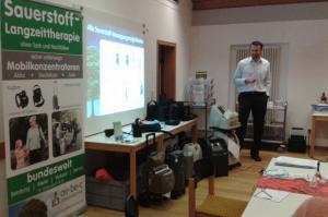 Ein Mitarbeiter hält einen Vortrag über mobile und stationäre Sauerstoffkonzentratoren in einer Selbsthilfegruppe - air-be-c Medizintechnik