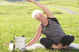 Eine Frau sitzt auf einer Wiese und macht Yoga. Neben ihr steht der FreeStyle Comfort - air-be-c Medizintechnik