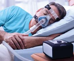 Ein Mann liegt im Bett und schläft. Er trägt eine Mund-Nasenmaske und auf dem Nachtschrank steht das Beatmungsgerät. - air-be-c Medizintechnik.