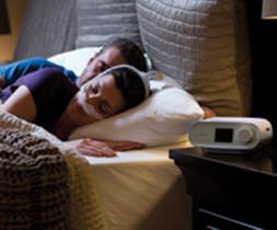 Ehepaar liegt im Bett und schläft. Frau trägt Nasalmaske und Schlaftherapiegerät steht auf dem Nachttisch. - air-be-c Medizintechnik