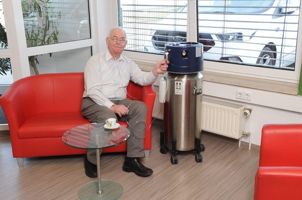 Ein älterer Herr sitzt auf dem Sofa und schließt die Nasenbrille am Basistank an. Flüssigsauerstoff für Zuhause