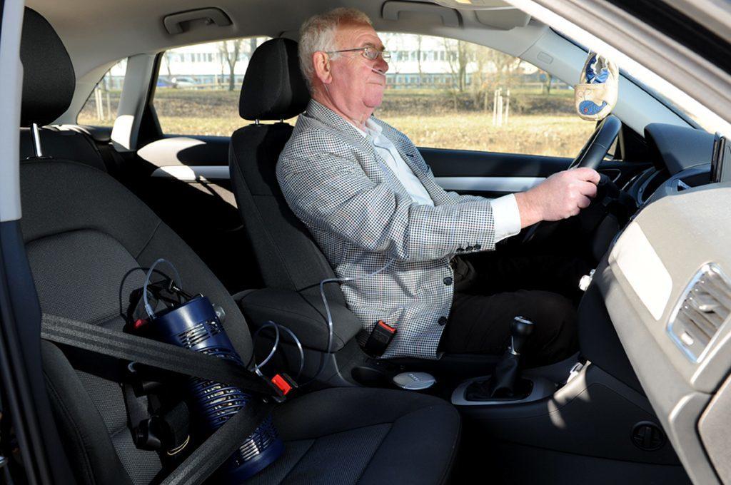 Ein Mann fährt mit dem Auto, den Sprint hat er auf dem Beifahrersitz mit dem Gurt gesichert. mobile Flüssigsauerstoffgeräte