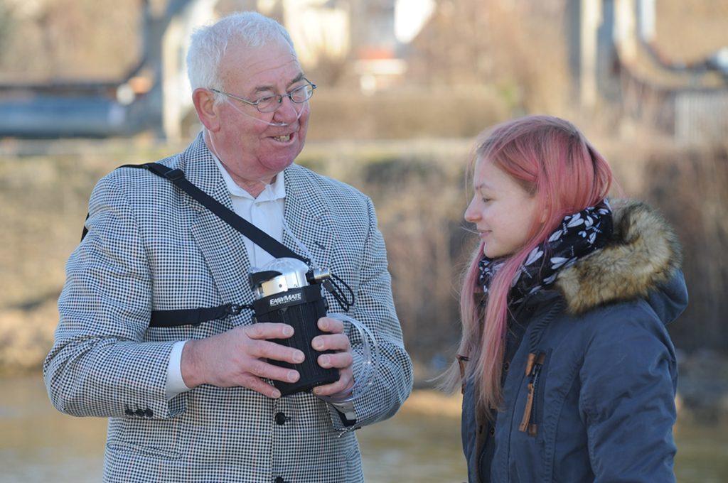 Ein Herr zeigt einer jungen Frau sein Mobilteil EasyMate Portable. tragbare Flüssigsauerstoffgeräte