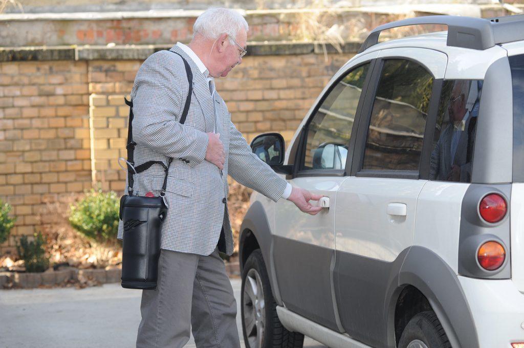 Ein Mann öffnet die Autotür. Er trägt den Spirit 1200 über der Schulter. tragbare Flüssigsauerstoffgeräte