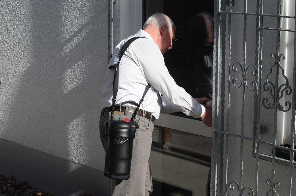 Ein Mann öffnet die Eingangstür. Er trägt den Spirit 1200 auf der Schulter. tragbare Flüssigsauerstoffgeräte