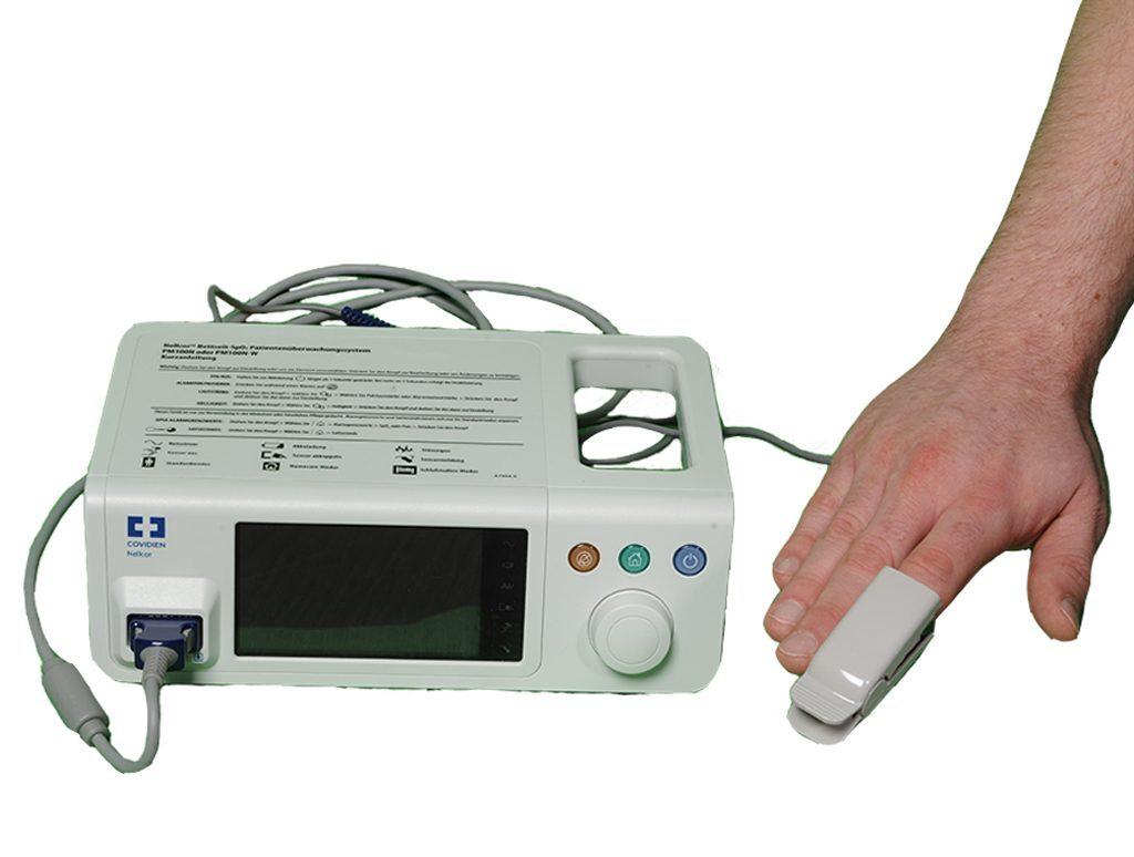 Überwachungssystem PM100N mit Fingerclip am Zeigefinger. Pulsoximeter