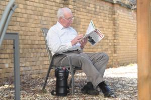 Ein älterer Herr sitzt im Hof und liest Zeitung. Neben seinem Stuhl steht der Spirit 1200.