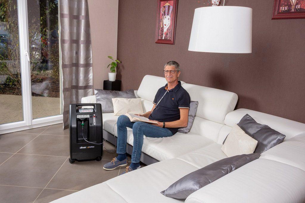 : Der stationäre Sauerstoffkonzentrator Compact 525 steht im Wohnzimmer neben dem Sofa auf dem ein Mann sitzt und ein Buch liest.