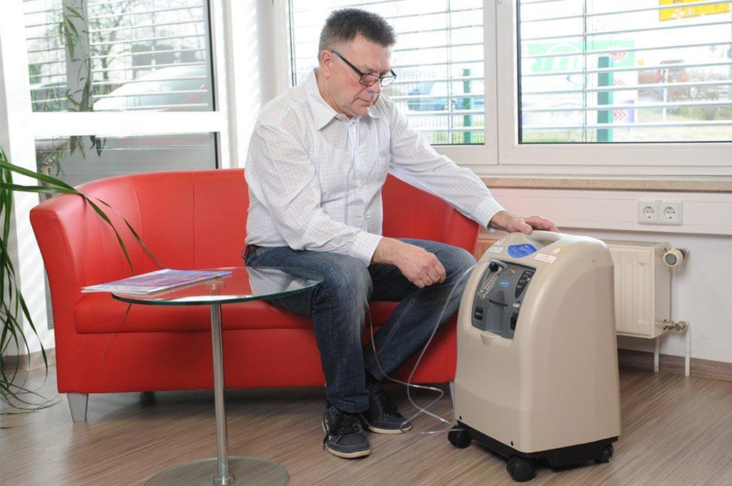 Ein Mann sitzt auf dem Sofa, neben ihm steht der Perfecto 2V. Er schließt gerade seine Nasenbrille an. stationärer Sauerstoffkonzentrator