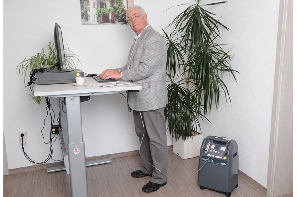 : Ein älterer Herr arbeitet an einem Steharbeitsplatz. Neben ihm steht der VisionAire 5. stationärer Sauerstoffkonzentrator