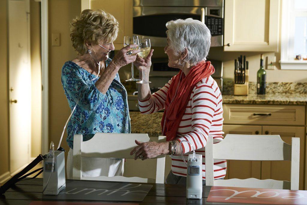 Zwei Frauen stehen in der Küche und prosten sich zu. Beide haben einen Inogen One G4 neben sich auf dem Tisch stehen. tragbarer Sauerstoffkonzentrator