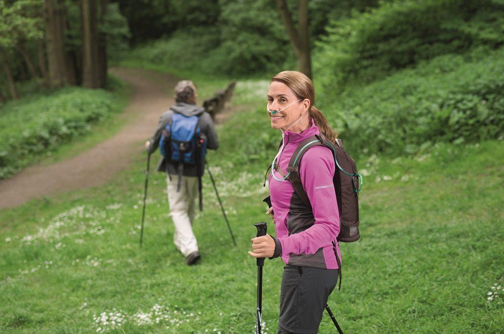 Eine Frau beim Wandern trägt den SimplyGo mini im Rucksack. tragbarer Sauerstoffkonzentrator