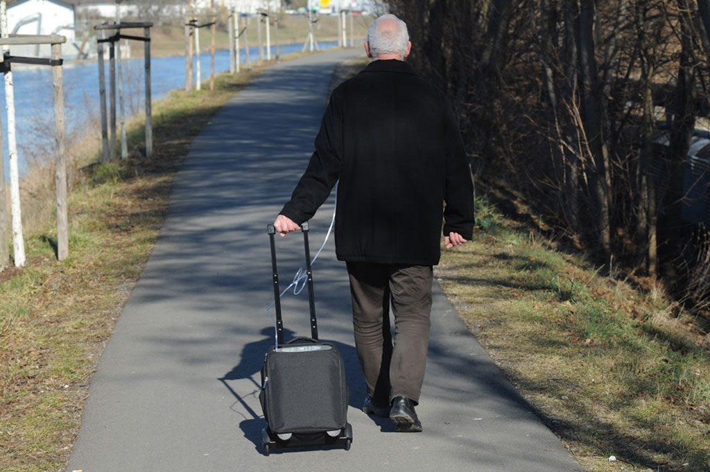 : Ein Mann geht am Ufer eines Flusses spazieren und zieht dabei den iGo hinter sich her. transportabler Sauerstoffkonzentrator