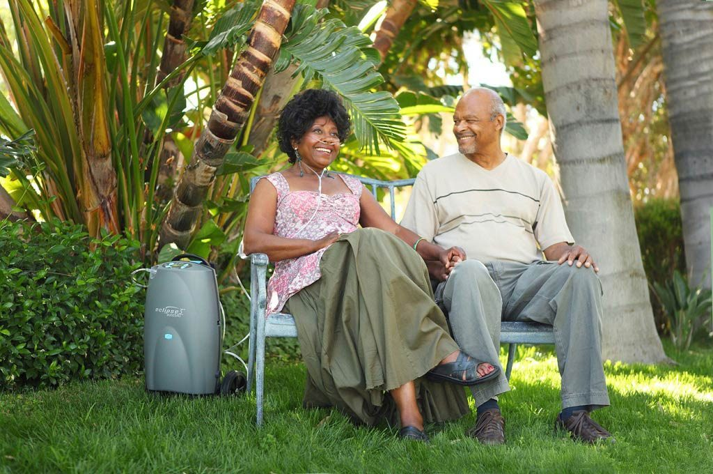 Ein Ehepaar sitzt unter Palmen auf einer Bank. Daneben steht der Eclipse 5. transportabler Sauerstoffkonzentrator