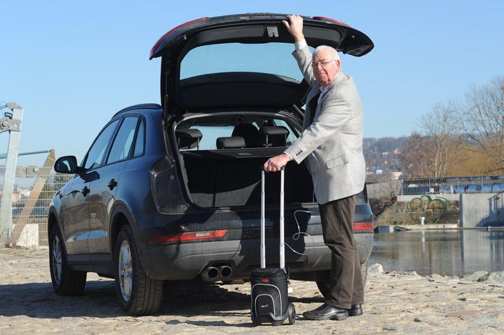 : Ein älterer Herr steht am geöffneten Kofferraum seines Autos und hält den Zen-O am Griff des dazugehörigen Trolleys. transportabler Sauerstoffkonzentrator