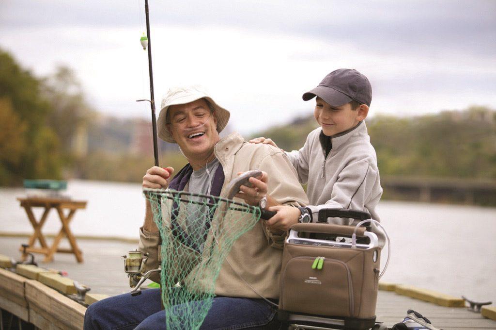 Ein Vater sitzt mit seinem Sohn auf einem Steg und Angelt. Sie haben im Köcher einen Fisch. Neben ihnen steht der SimplyGo in seiner Tragetasche. transportabler Sauerstoffkonzentrator