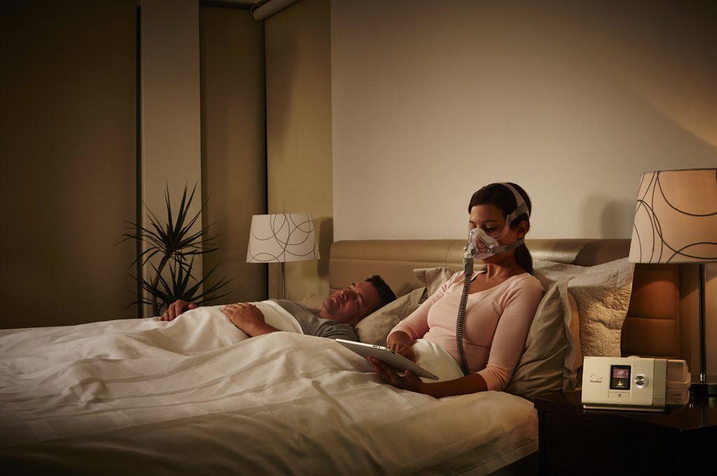 Patientin sitzt im Bett und benutzt das CPAP Gerät