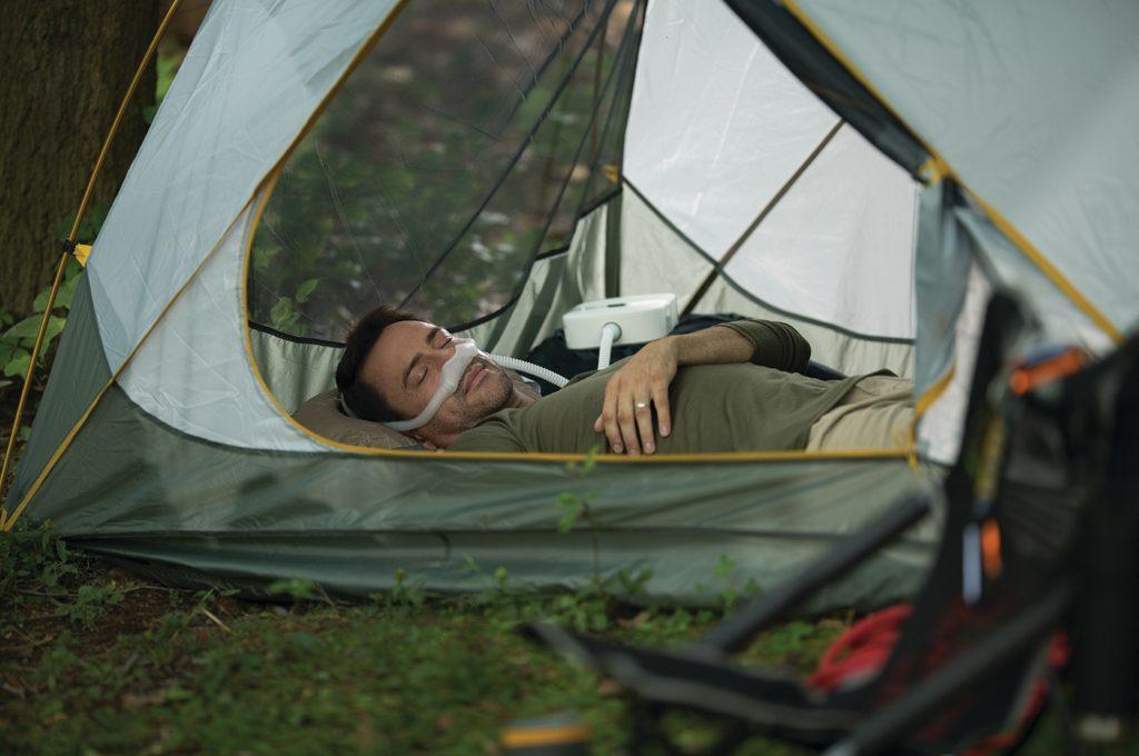Patient liegt im Zelt und benutzt das CPAP Gerät