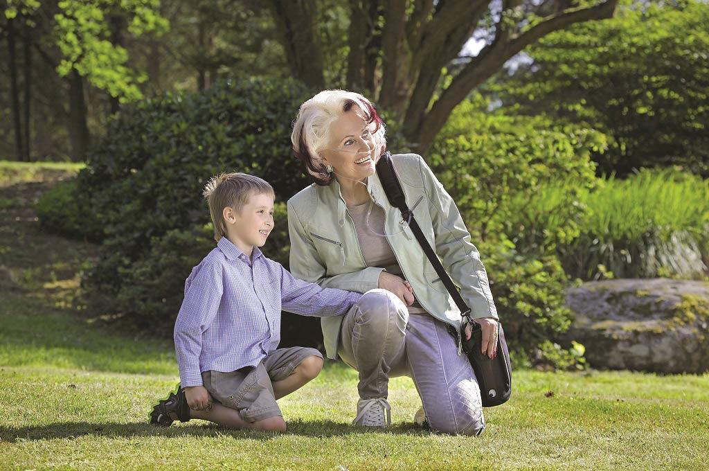 Eine Frau hockt mit ihrem Enkelkind im Park. Sie trägt den Zen-O lite in der Tragetasche und hat ihn um die Schulter gehängt - tragbarer Sauerstoffkonzentrator