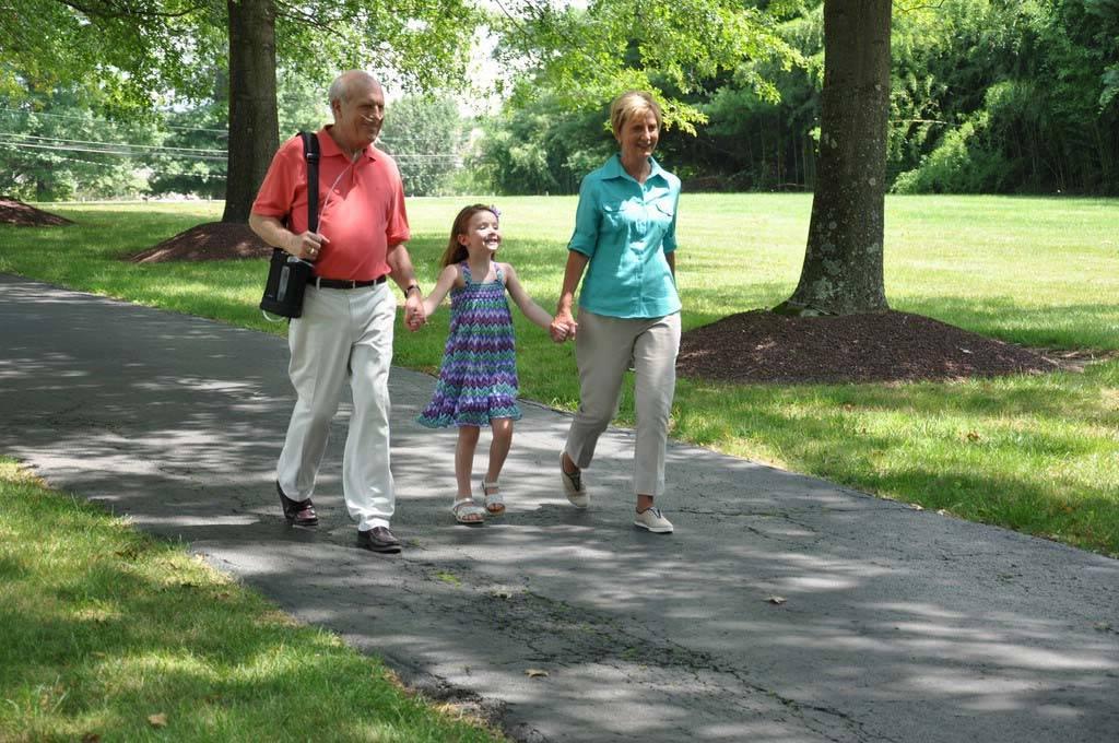 Oma und Opa spazieren mit dem Enkel durch einen Park. Der Opa trägt den Inogen One G3 auf seiner rechten Schulter. tragbarer Sauerstoffkonzentrator