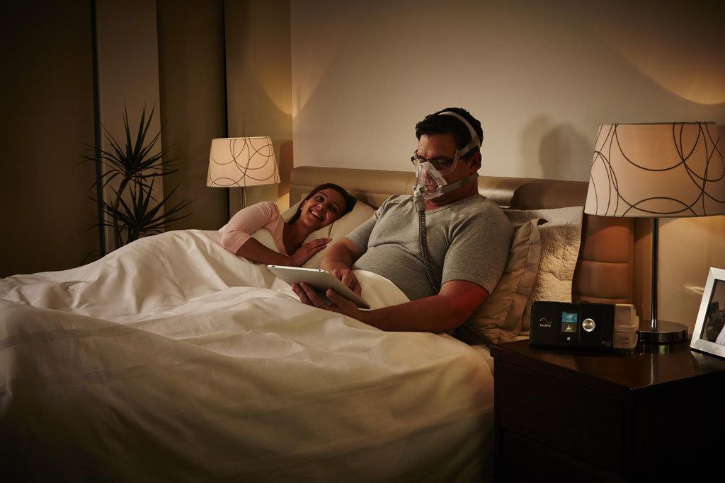 Patient sitzt im Bett und benutzt ein APAP Gerät