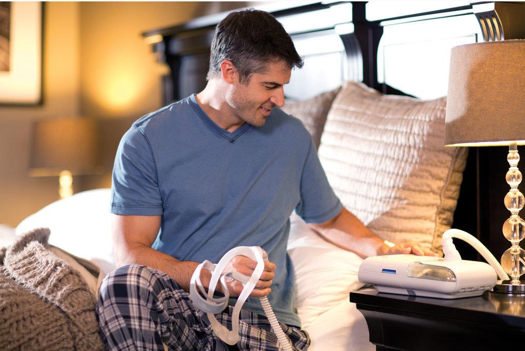 Mann sitzt am Bett und bedient ein ASV Gerät